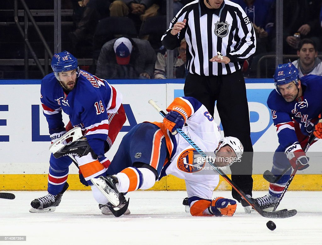 Casey Cizikas #53 of the New York Islanders is tripped up during the second period faceeoff against the New York Rangers at Madison Square Garden on March 6, 2016 in New York City.