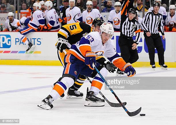 Casey Cizikas of the New York Islanders reaches for the puck as David Warsofsky of the Pittsburgh Penguins plays defense at PPG PAINTS Arena on...