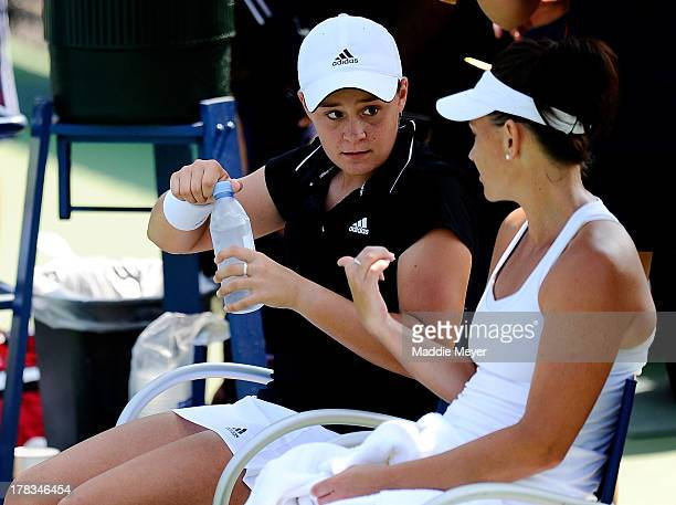 Casey Dellacqua of Australia and Ashleigh Barty of Australia talk during a break in their women's doubles first round match against Sorana Cirstea of...