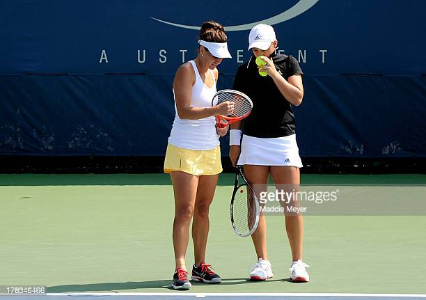 Casey Dellacqua of Australia and Ashleigh Barty of Australia talk tactics during their women's doubles first round match against Sorana Cirstea of...