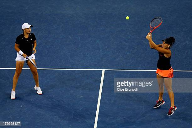 Casey Dellacqua of Australia smashes the ball next to her partner Ashleigh Barty during their women's doubles final match against Andrea Hlavackova...