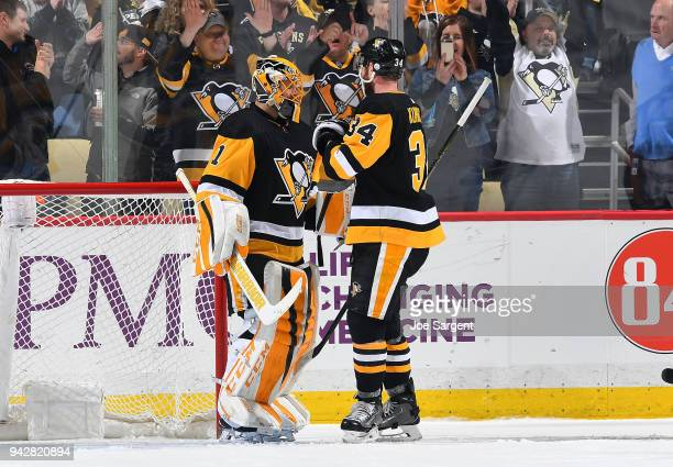 Casey DeSmith celebrates with Tom Kuhnhackl of the Pittsburgh Penguins after a 40 win over the Ottawa Senators at PPG Paints Arena on April 6 2018 in...