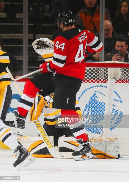 Casey DeSmith of the Pittsburgh Penguins makes a glove save while being screened by Miles Wood of the New Jersey Devils during the game at Prudential...