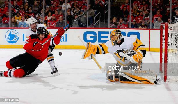 Casey DeSmith of the Pittsburgh Penguins makes a save as Brian Dumoulin checks Brian Boyle of the New Jersey Devils during the game at Prudential...