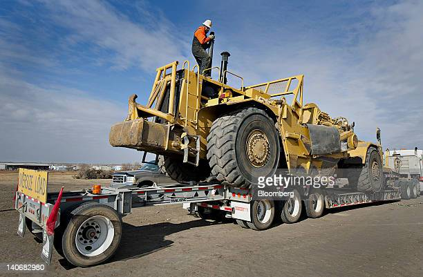 Casey Gallue a field mechanic for Knife River Corp removes an exhaust stack from a Caterpillar Inc 627G Scraper after loading it for transport for...