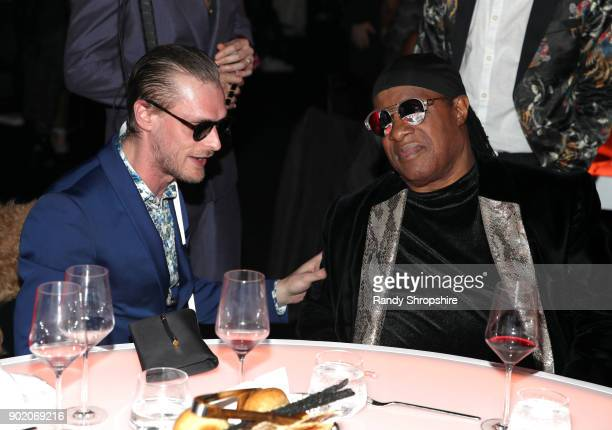 Casey Harris and Stevie Wonder attend The Art of Elysium presents John Legend's HEAVEN at Barker Hangar on January 6 2018 in Santa Monica California