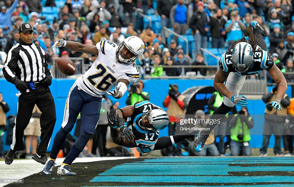Casey Hayward #26 of the San Diego Chargers lunges for a tipped pass against Devin Funchess #17 and teammate Kelvin Benjamin #13 of the Carolina Panthers in the first quarter during the game at Bank of America Stadium on December 11, 2016 in Charlotte, North Carolina.