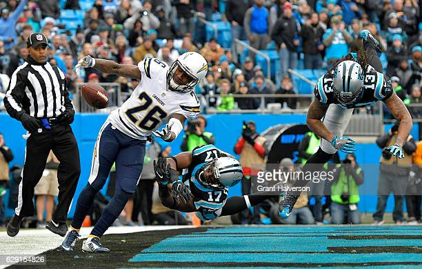 Casey Hayward of the San Diego Chargers lunges for a tipped pass against Devin Funchess and teammate Kelvin Benjamin of the Carolina Panthers in the...