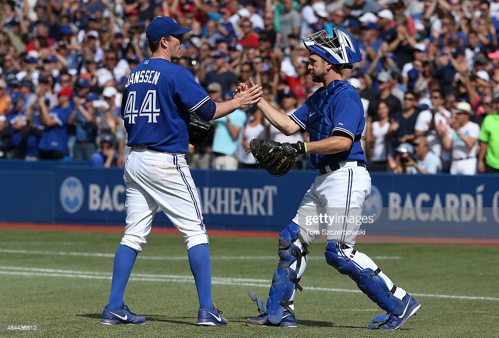 Casey Janssen #44 of the Toronto Blue Jays celebrates their victory with Josh Thole #30 during MLB game action against the New York Yankees on August 31, 2014 at Rogers Centre in Toronto, Ontario, Canada.