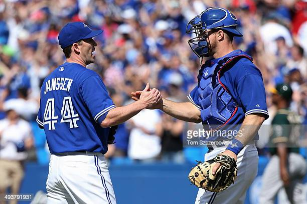 Casey Janssen of the Toronto Blue Jays celebrates their victory with Erik Kratz during MLB game action against the Oakland Athletics on May 25 2014...