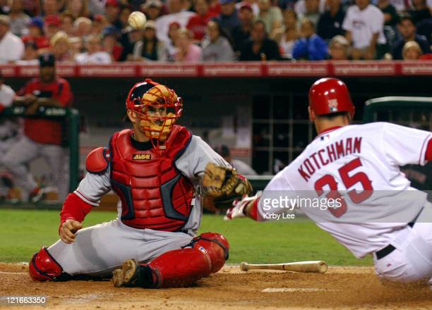 Casey Kotchman of the Los Angeles Angels of Anaheim slides safety into home plate after a bobbled throw to Boston Red Sox catcher Jason Varitek in...