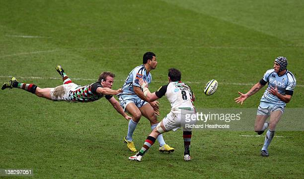 Casey Laulala of Cardiff hands off to teammate Tom James as he is tackled by Will Skinner and Tom Guest of Quins during the LV= Cup match between...
