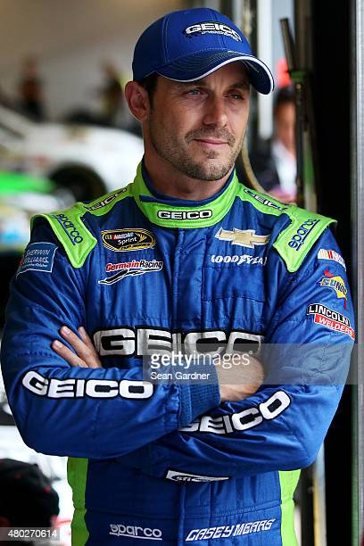 Casey Mears driver of the GEICO Chevrolet stands in the garage area during practice for the NASCAR Sprint Cup Series Quaker State 400 Presented by...