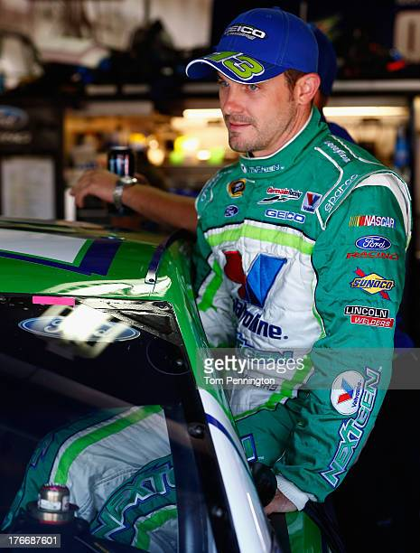 Casey Mears driver of the Valvoline NextGen Ford climbs into his car during practice for the NASCAR Sprint Cup Series 44th Annual Pure Michigan 400...