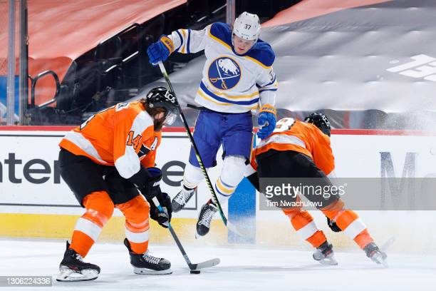 Casey Mittelstadt of the Buffalo Sabres leaps between Sean Couturier and Robert Hagg of the Philadelphia Flyers during the second period at Wells...