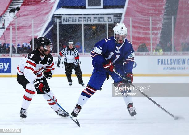 Casey Mittelstadt of United States skates up ice with the puck as Dillon Dub of Canada pursues in the first period during the IIHF World Junior...