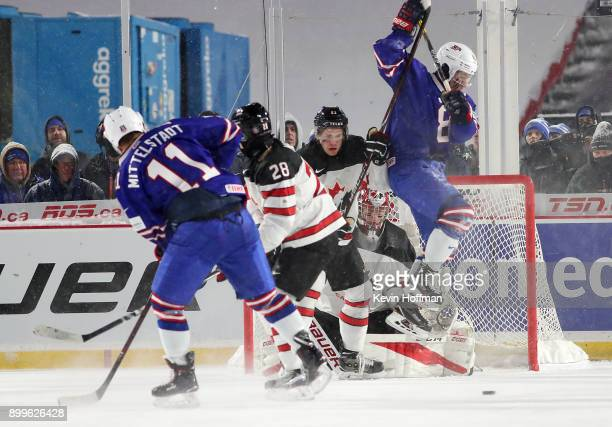 Casey Mittelstadt of United States takes a shot as Adam Fox jumps to screen Carter Hart of Canada during the IIHF World Junior Championship at New...