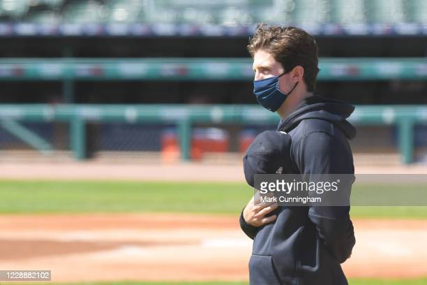 Casey Mize of the Detroit Tigers looks on during the National Anthem while wearing a face mask prior to the game against the Cleveland Indians at...