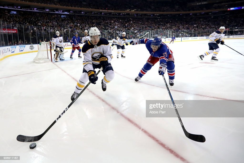 Casey Nelson #8 of the Buffalo Sabres and Jesper Fast #17 of the New York Rangers reach for the puck in the second period during their game at Madison Square Garden on January 18, 2018 in New York City.