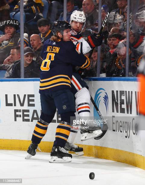 Casey Nelson of the Buffalo Sabres checks Alex Chiasson of the Edmonton Oilers into the boards during an NHL game on March 4 2019 at KeyBank Center...
