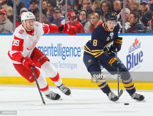 Casey Nelson of the Buffalo Sabres controls the puck against Anthony Mantha of the Detroit Red Wings during an NHL game on March 29 2018 at KeyBank...