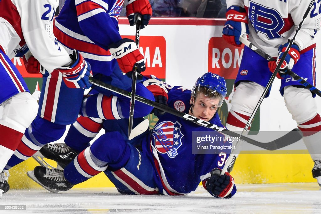 Casey Nelson #34 of the Rochester Americans falls to the ice against the Laval Rocket during the AHL game at Place Bell on October 25, 2017 in Montreal, Laval, Canada.