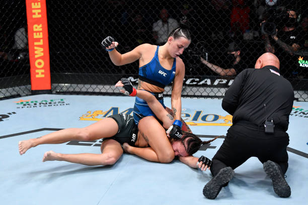 Casey O'Neill of Australia punches Antonina Shevchenko of Kyrgyzstan in their women's flyweight bout during the UFC Fight Night event at UFC APEX on...