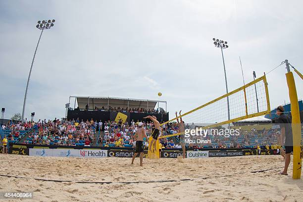 Casey Patterson spikes the ball against Jeremy Casebeer and Casey Jennings as Jake Gibb looks on at the 2014 AVP Cincinnati Open on August 30 2014 at...
