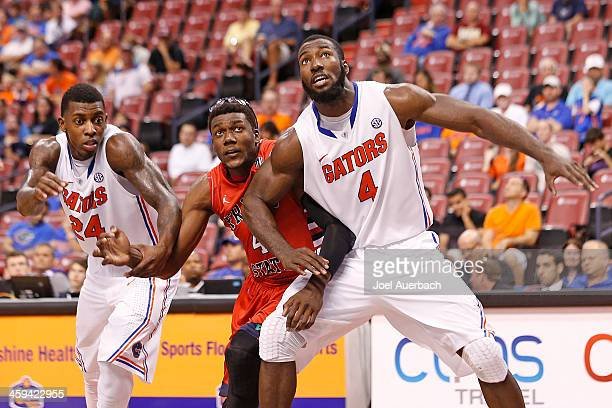 Casey Prather and Patric Young of the Florida Gators block out Karachi Edo of the Fresno State Bulldogs during the MetroPCS Orange Bowl Basketball...