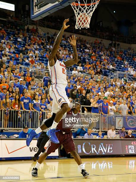 Casey Prather of the Florida Gators attempts a shot over Kemy Osse of the Arkansas Little Rock Trojans during the game at Stephen C O'Connell Center...