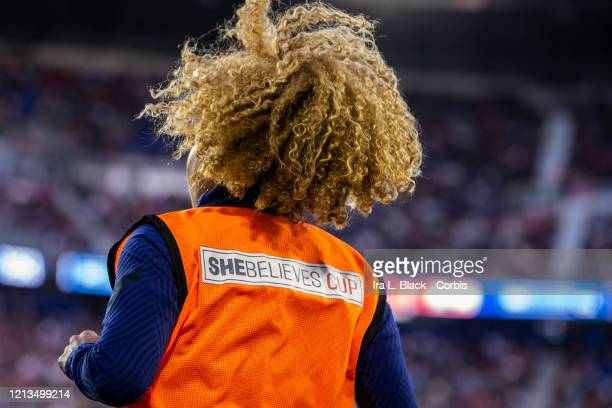 Casey Short of the United States from that back as she warms up on the sideline with her hair flowing in the wind while she wears an orange bib with...