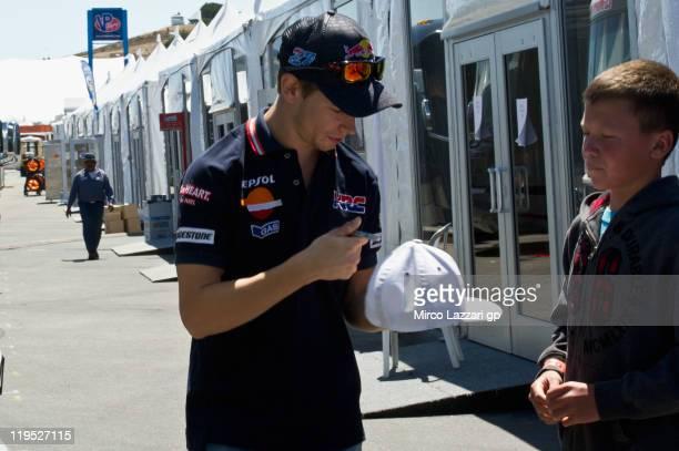 Casey Stoner of Australia and Repsol Honda Team signs autograph for fan in paddock during the Red Bull U.S. Grand Prix at Mazda Raceway Laguna Seca...