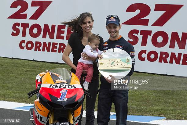 Casey Stoner of Australia and Repsol Honda Team with his wife Adriana and his daughter Alessandra Maria pose with his bike in turn 3 during the...