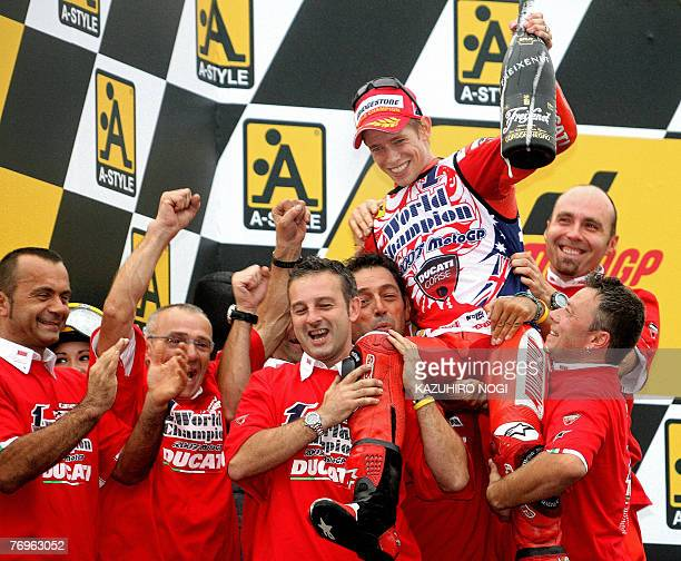 Casey Stoner of Australia, Ducati Marlboro team, is lifted by his team members as he celebrates his first world motorcycling championship title at...