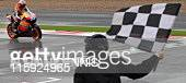 Casey Stoner of Australia rides through the finish line to take the chequered flag to win the MotoGP motorcycle race during the British Grand Prix at...