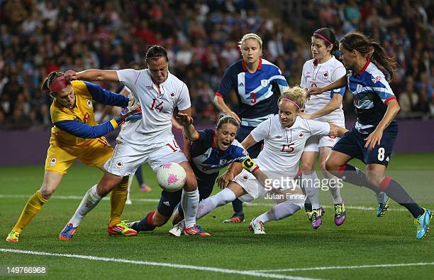 Casey Stoney of Great Britain goes down in the penalty box with pressure from Melissa Tancredi of Canada and Kelly Parker of Canada during the...