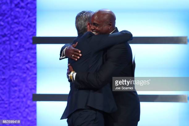 Casey Wasserman and Carl Lewis hug on stage during the 2017 Team USA Awards on November 29 2017 in Westwood California
