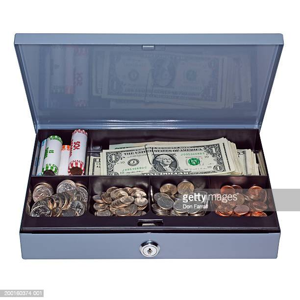 Cash box filled with assorted US currency, elevated view