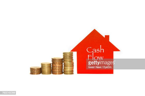Cash Flow Text On Red House By Stack Of Coins Against White Background