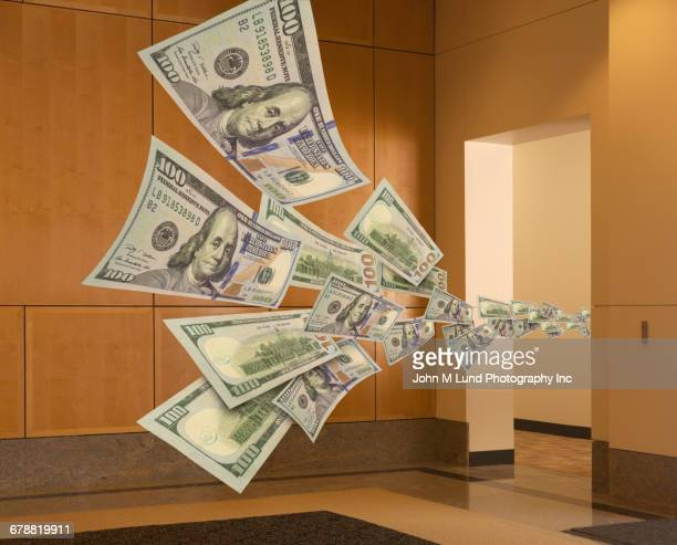 Cash flowing through office doorway