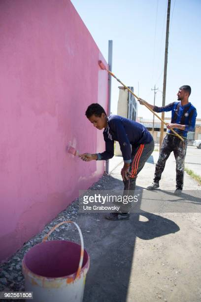 Cash for work Painters paint a wall at a school rehabilitated with BMZ funds in West Mosul on April 24 2018 in MOSUL IRAQ