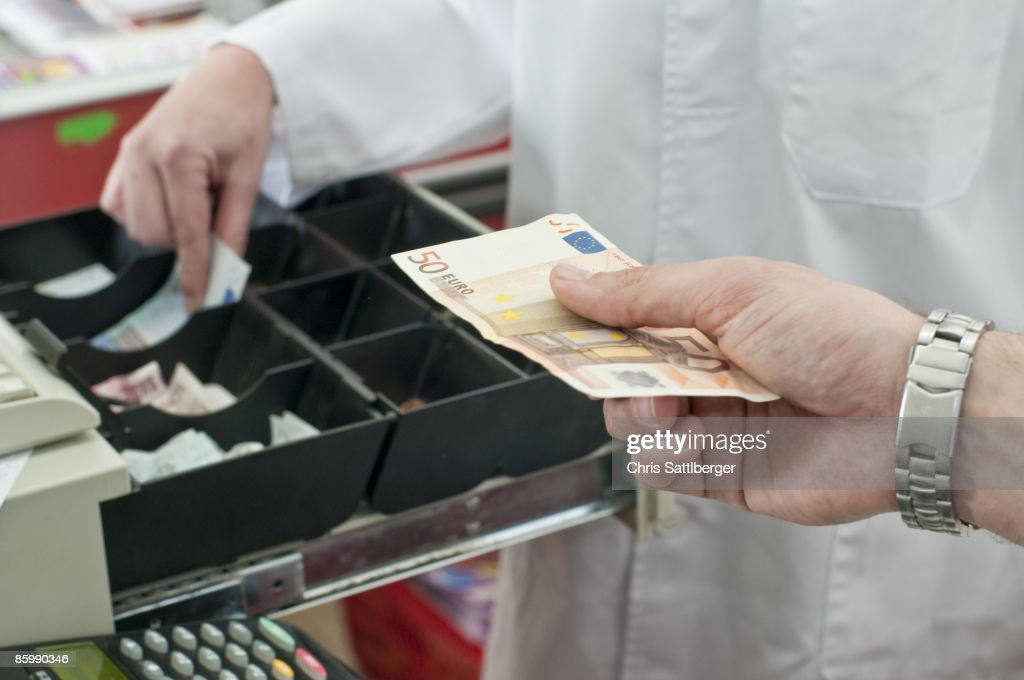 cash in hand of customer paying in supermarket : Stock Photo
