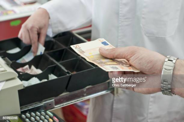 cash in hand of customer paying in supermarket - billet de 50 euros photos et images de collection