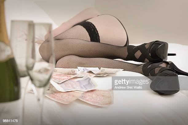 cash, next to woman on bed in stockings & heels - hoeren stockfoto's en -beelden