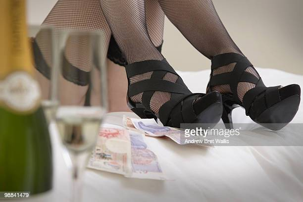cash next to woman on bed in stockings & heels