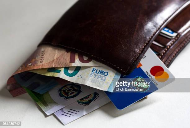 Cash or credit card which method of payment will prevail in the future The picture shows a purse with euro banknotes and a Mastercard credit card