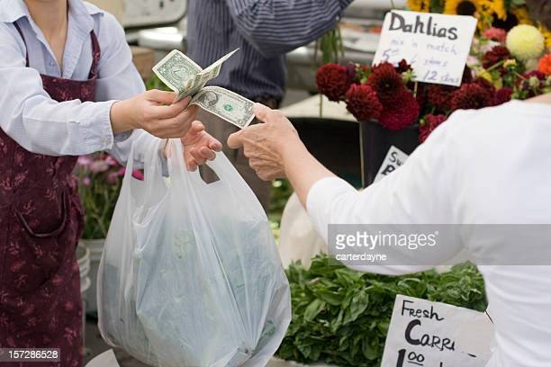 Cash payment for purchase at a farmers market.