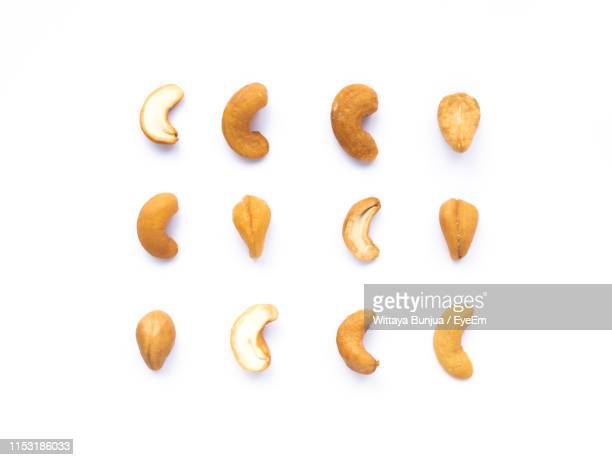 cashews against white background - cashew stock pictures, royalty-free photos & images