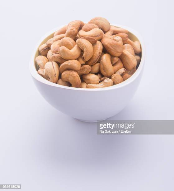 cashews in bowl over white background - cashew stock pictures, royalty-free photos & images
