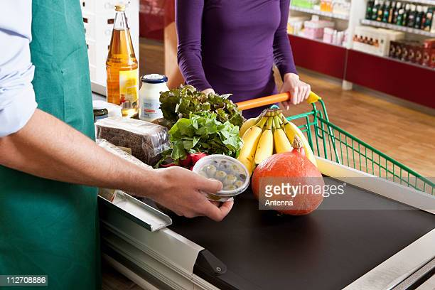 a cashier and customer at the checkout line of a supermarket, midsection - cashier stock pictures, royalty-free photos & images